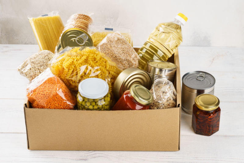 Various canned food, pasta and cereals in a cardboard box.